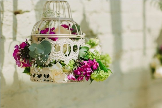 Hanging birdcages filled with summer flowers